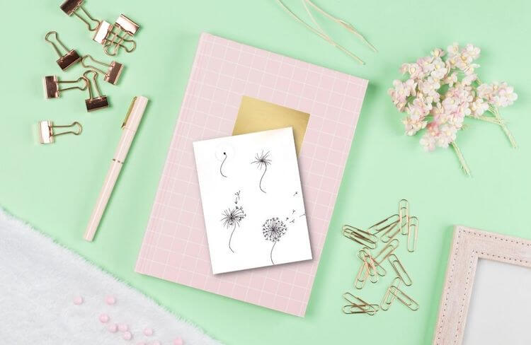 Bullet journal doodles   Image shows a pale green desk with stationery on it, including dandelion bullet journal doodles.