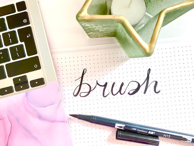 Bullet journaling fonts | image shows the word 'brush' written in black brush font, next to an open brush pen, a laptop with a marbled pink keyboard, and a green star-shaped candle.
