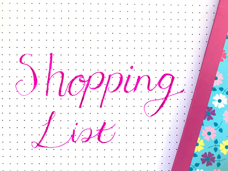 The words 'shopping list' written in pink faux calligraphy. There's a flowery notebook in the background.