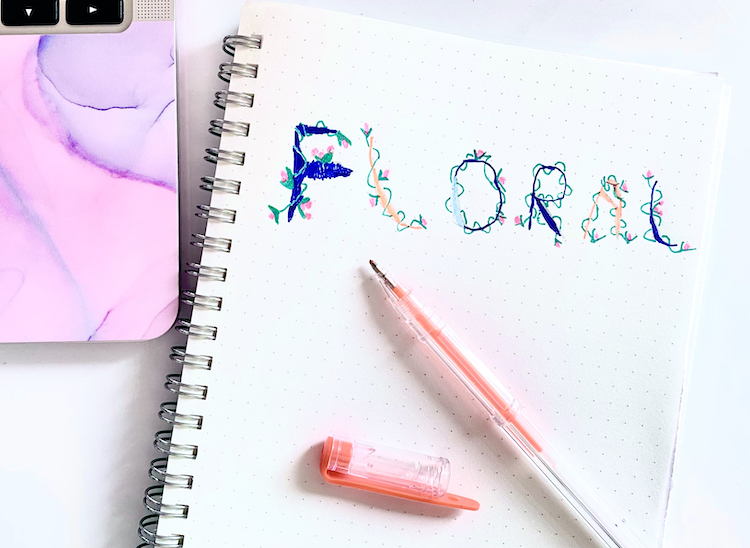 The word 'floral' written in caps, with a floral design. There's an orange pen laying beneath the writing.