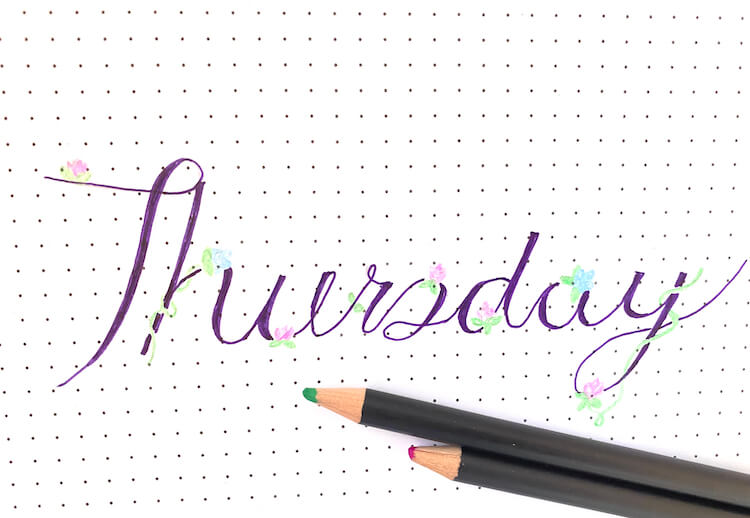 'Thursday' written in cursive text and decorated with blue and pink flowers. A green and pink pencil lie beneath the writing.