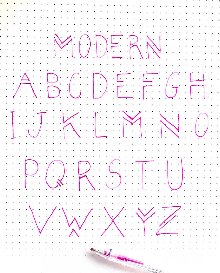 The word 'modern' and the alphabet written in purple modern font. The open purple pen is in the foreground.