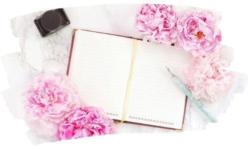 Bullet journaling | Image shows an open journal beside pink carnations and a blue pen.