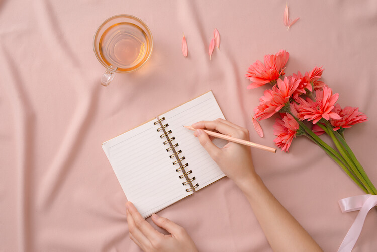 How to Journal   Image shows a woman writing in a journal with a peach background and a cup of tea beside her.