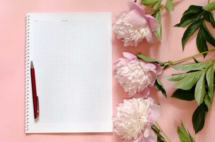 How to write a journal   Image shows a journal and pen on a pink background beside some pink peonies.