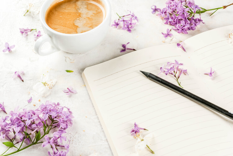 Journal beside a cup of tea and some purple flowers.