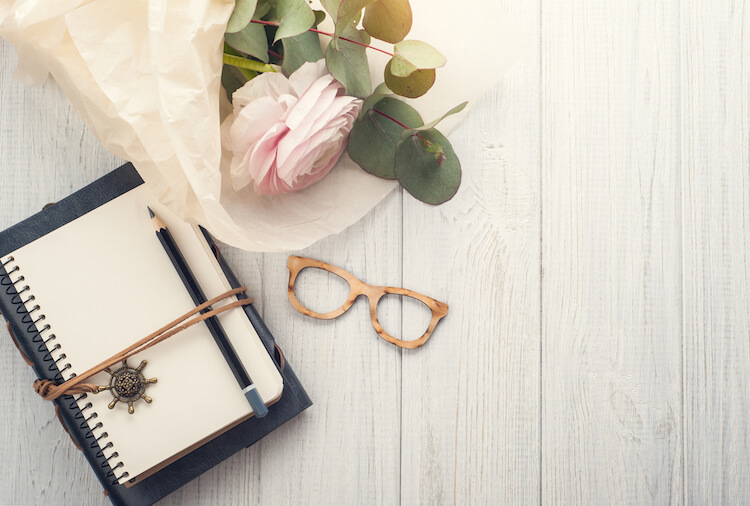 How to keep a journal   Image shows a journal beside some glasses and a bunch of pink carnations on a pale wood background..
