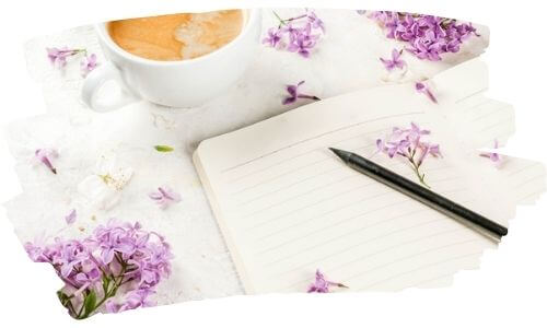 Journal Prompts | Image shows an open journal beside purple flowers and a cup of coffee.