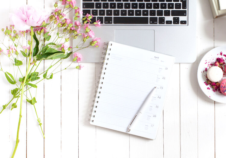 Journaling daily | Image shows an open diary and pen beside some pink flowers and macarons, on top of a laptop keyboard and white disk.