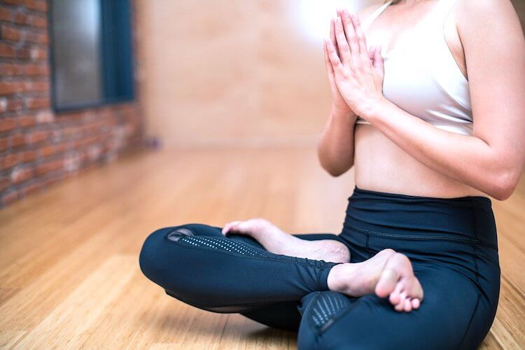 Image shows a woman in Lotus pose.