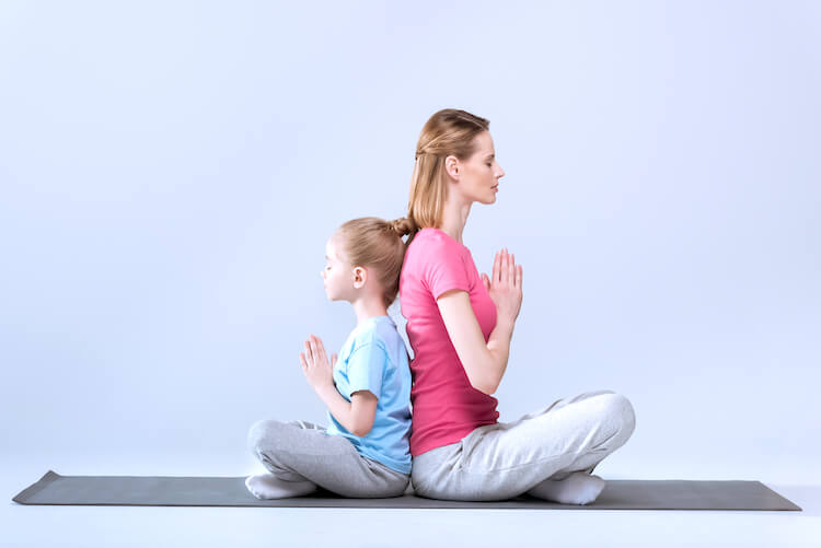 Meditation for inner child | Image shows a mother and daughter performing meditation back to back.