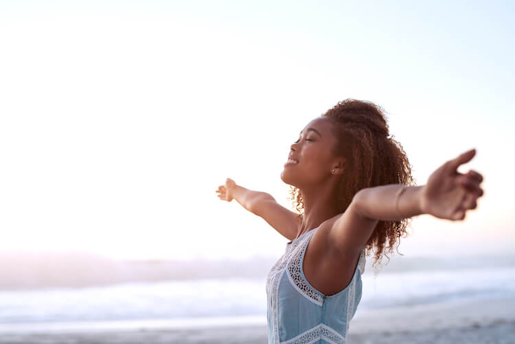 Positive thinking quotes | Image shows a black woman by the sea with her face upturned to the sky and her arms out wide.