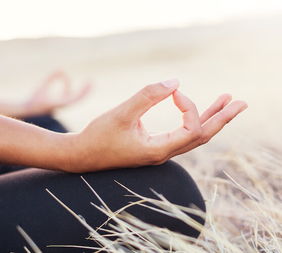 Reparenting exercises   Image shows a woman holding her thumb and finger together during meditation. She's sitting in a corn field and wearing black trousers.