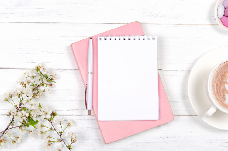Shadow work journaling   Image shows a pink journal with a pad and pen on top of it. There's a coffee cup in shot and some flowers, on a white background.