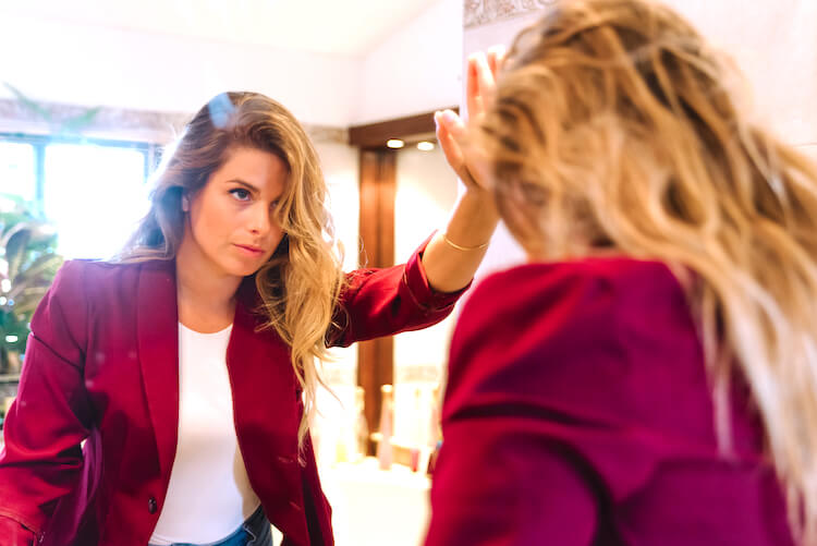 A woman with long and wavy blonde hair peers in a mirror looking pensive. She wears a red blazer over a white top and has one hand resting on the mirror.