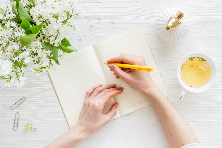 Image shows a woman writing in a diary with a cup of herbal tea to her right and some white flowers to her left.