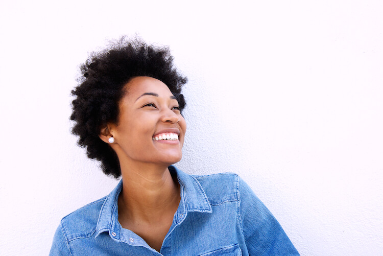 Affirmation for confidence   Image shows a black woman wearing a blue denim shirt and looking up to her left, with a relaxed and happy smile on her face.