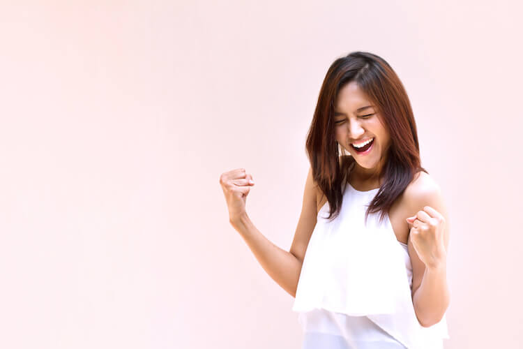 Confidence affirmations   Image shows a confident woman smiling and air-grabbing.