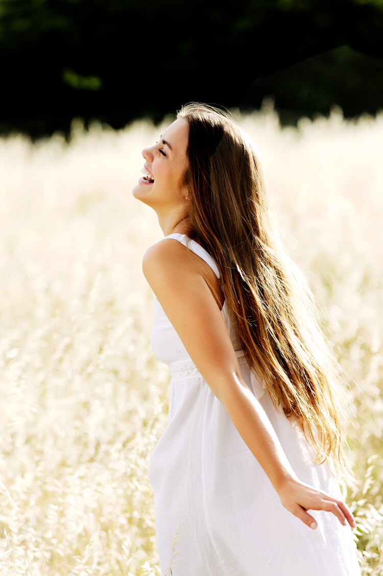 Image shows a young, carefree woman smiling and running through a corn field in a white dress.