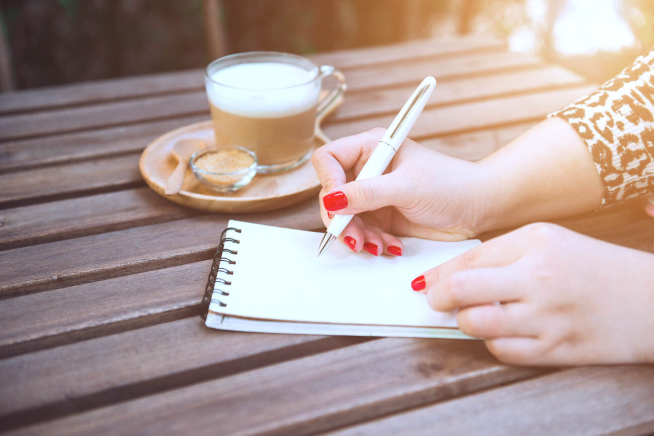 A woman with red painted nails and leopard print sleeves writes in a notepad. She has a cup of coffee on the wooden table top beside her.
