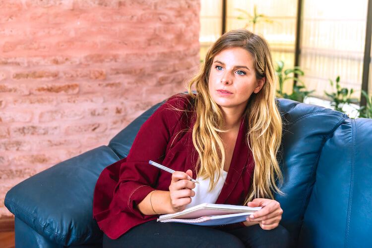 A woman with long and wavy blonde hair wearing a red blazer over a white top sits on a navy couch. She is holding a notebook and poised pen and looking pensive.