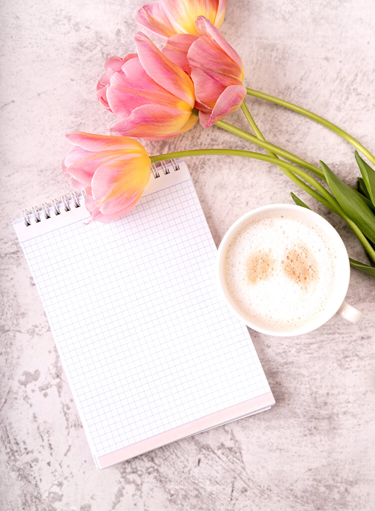 An open notebook lies on a a marble desktop. There are some peach and yellow tulips and a frothy cup of coffee beside it.