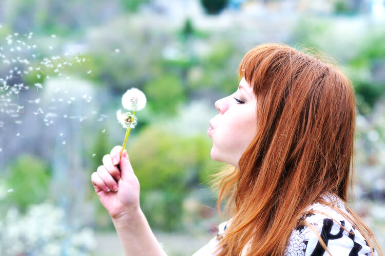 Healthy mindset | Image shows a woman with red hair blowing a dandelion clock.