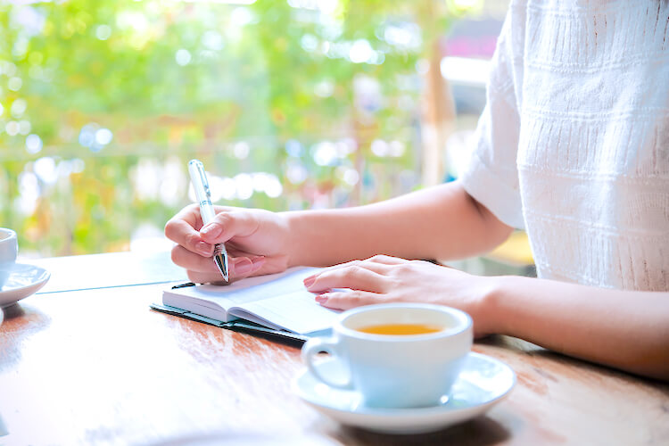 Shadow work affirmations | Image shows a woman writing. She has a cup of herbal tea beside her and there's green foliage outside of the window.