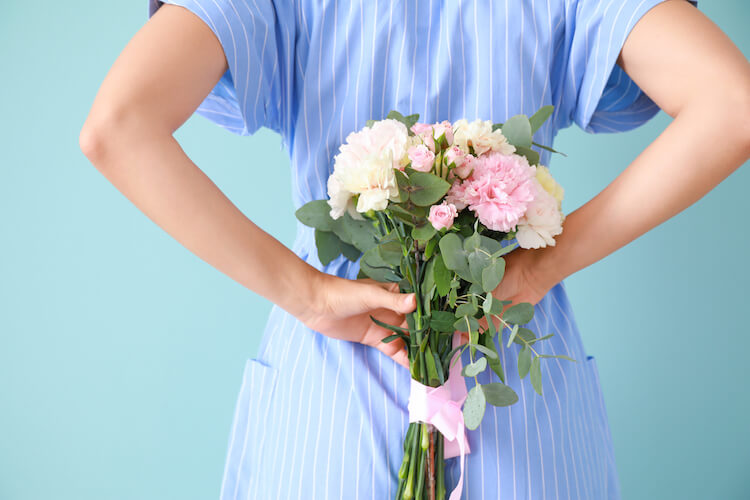 Image shows a woman in a blue dress holding a bouquet of flowers behind her back.