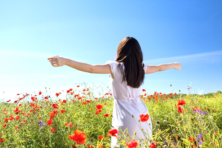 Affirmations for gratitude | Image shows a young woman with long dark hair in a poppy field with arms outstretched.