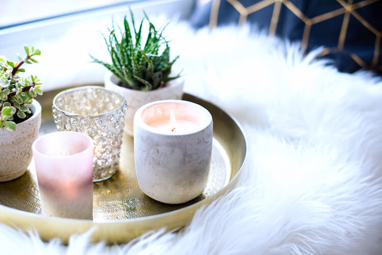 Image shows tea lights and miniature plants on a gold tray placed upon a furry white blanket.