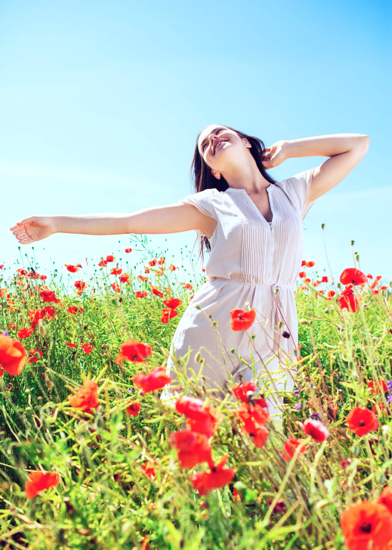 Gratitude affirmations | Image shows a young woman with long dark hair in a poppy field with arms outstretched.