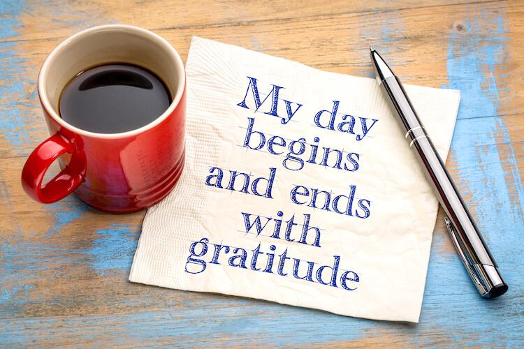 Attitude of gratitude quote beside a red mug.