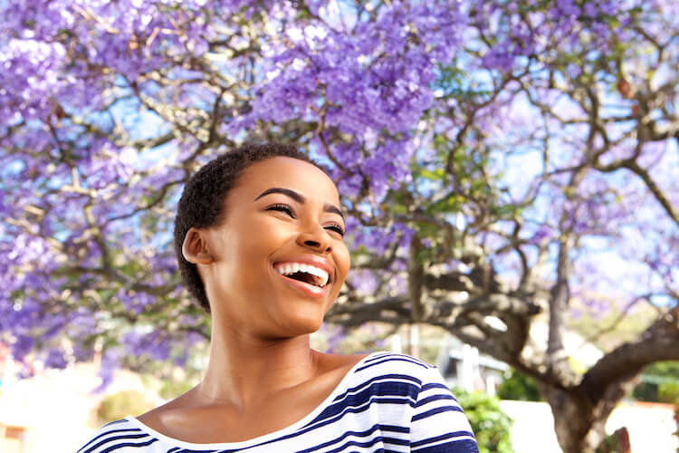 Image shows a beautiful black woman smiling in front of purple blossom.