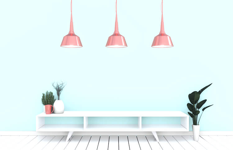 Image shows a white table beside a plant in a white pot, against a pale blue wall. There are three copper coloured downlights hanging above.