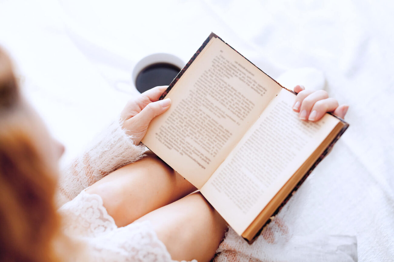 Quotes about simple life. Image shows a woman reading with a cup of black coffee beside her.