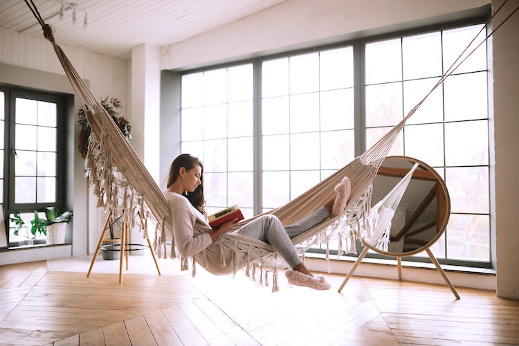 Image shows a woman reading in a hammock, placed in front of a large window.