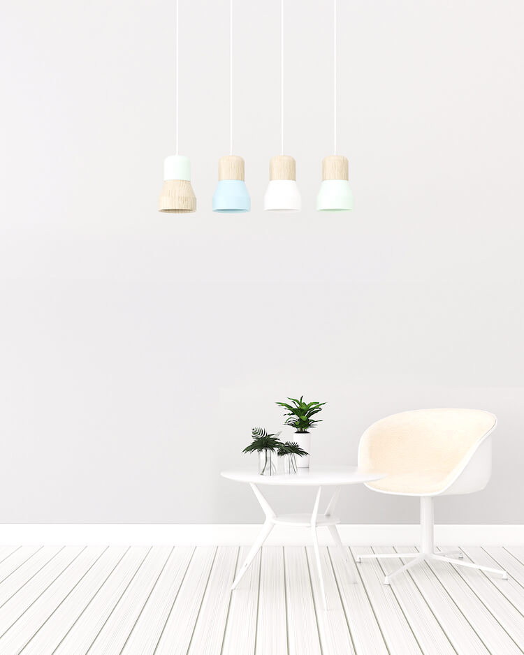Simpler life | Image shows a white tub chair and small white table with a plant on it. There are four pastel coloured downlights hanging above.