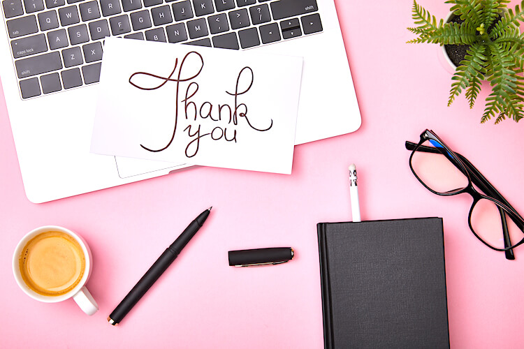 A thank you note placed on top of an open laptop. There's a cup of coffee, a pair of glasses, a notebook and a plant laid out on the pink background.