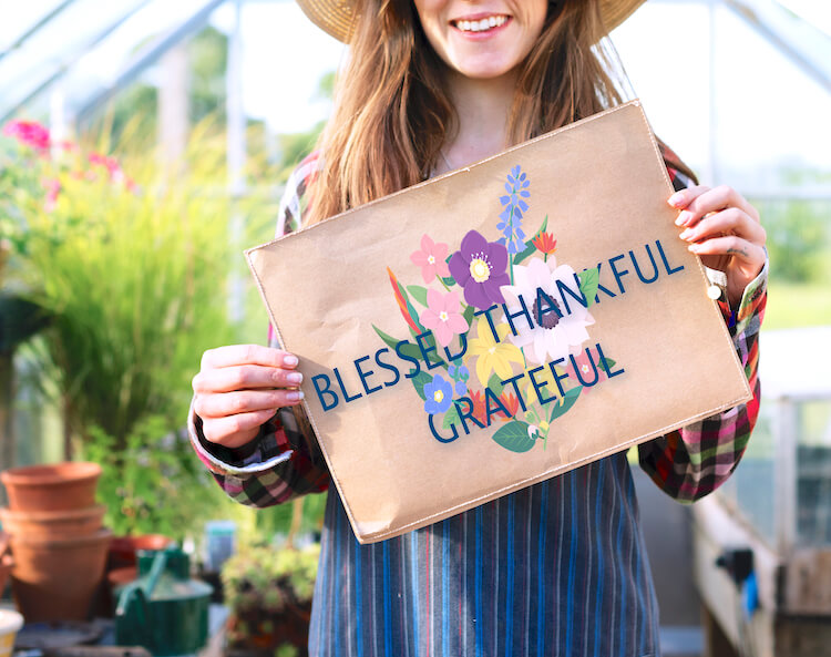 Image shows a woman standfing in a greenhouse wearing a straw hat and holding a sign saying 'blessed, thankful, grateful'.