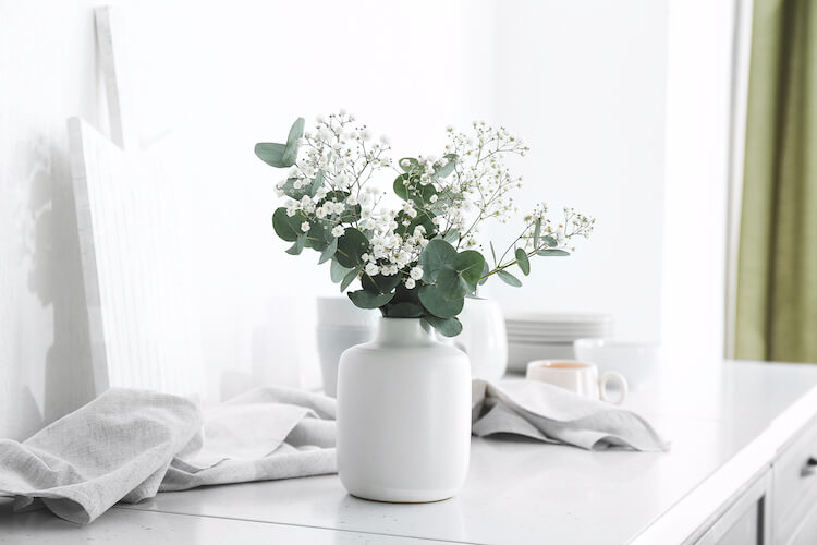 Image shows a white plant pot containing a plant with white flowers, against a white background.
