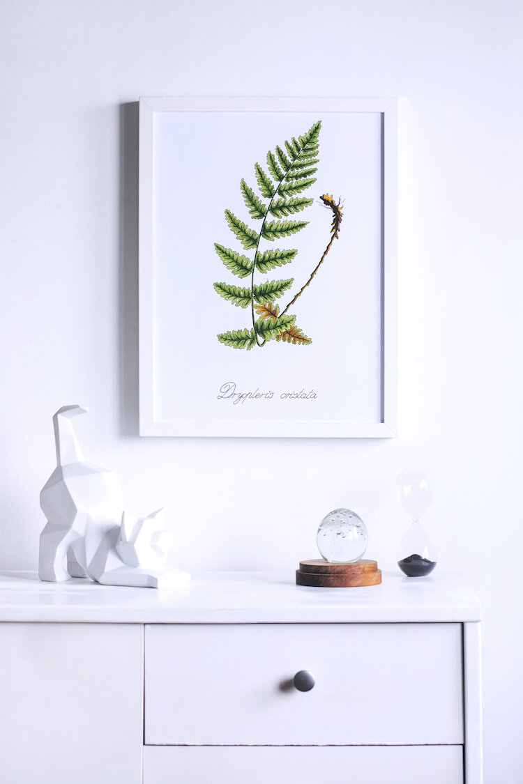 Image shows an art print of a leaf hanging on a white wall, above a white table with a white sculpture of a cat on it.