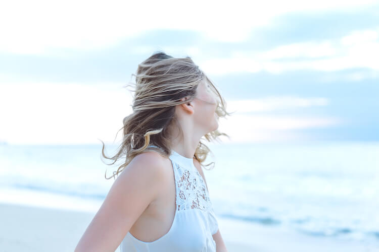 Why is personal development important | Image show a woman facing the sea with her hair whipping around her face.