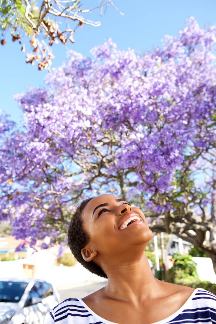 Image shows a beautiful black woman smiling and looking up at purple blossom.