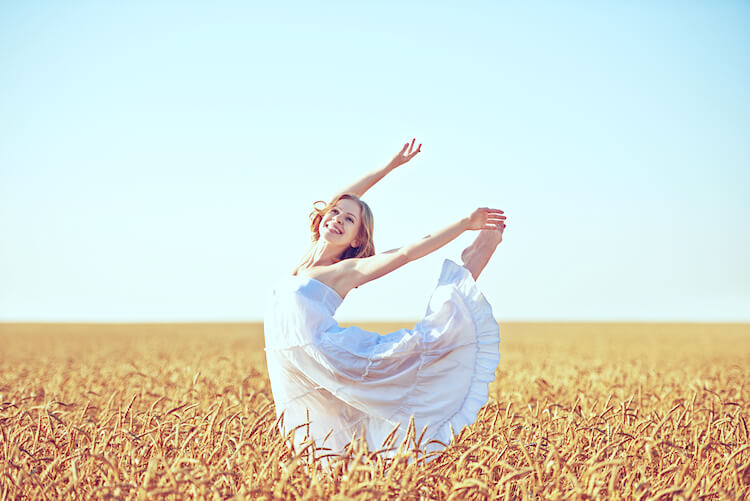 Affirmations of gratitude | Image shows a woman dancing in a wheat field.