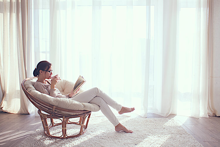 Image shows a woman reclining on a chair on front of a window. She is reading and holding a hot drink.