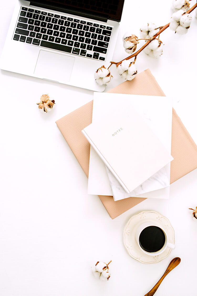 Journal manifestation | Image shows a stack of notebooks beside an espresso. There's a vine of flowers and a laptop in the background.