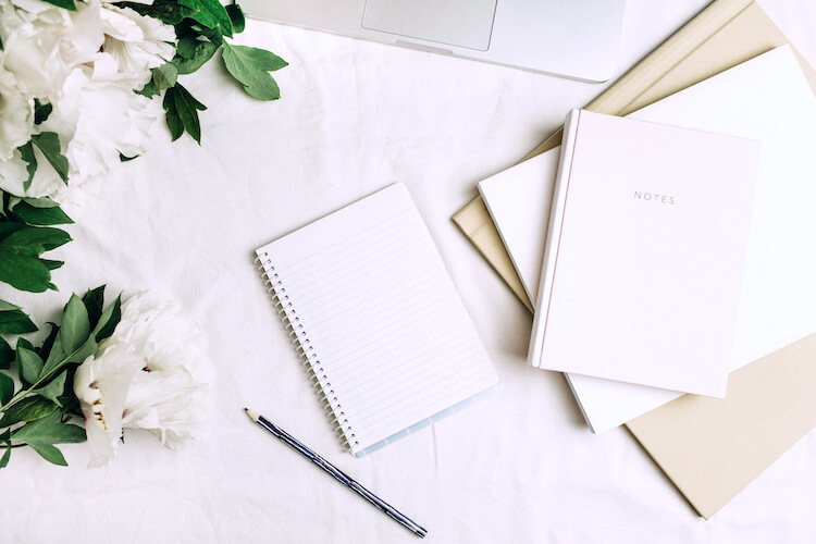 Journaling for manifestation | Image shows an open journal on a desk, beside white carnations and a pen.