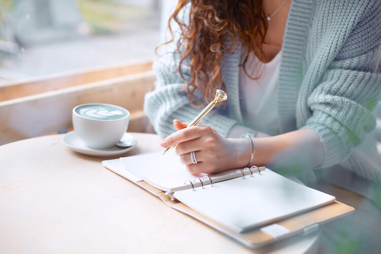 Manifestation journaling | Image shows a woman in a blue cardigan writing in a journal.