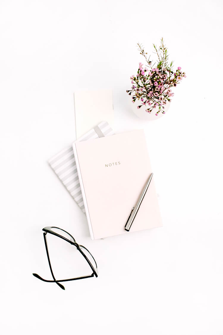 Manifestation journals | Image shows a pen on top of a stack of notebooks. There's a pair of glasses and a pot plant beside the notebooks.